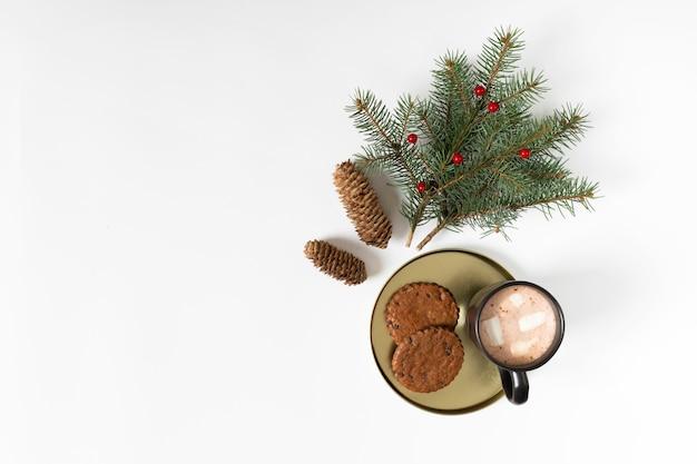 Filiżanka kawy z ciasteczka i gałąź drzewa jodły