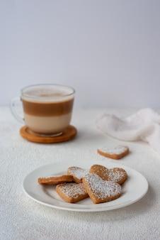 Filiżanka kawy z ciasteczkami domowej roboty w kształcie serca