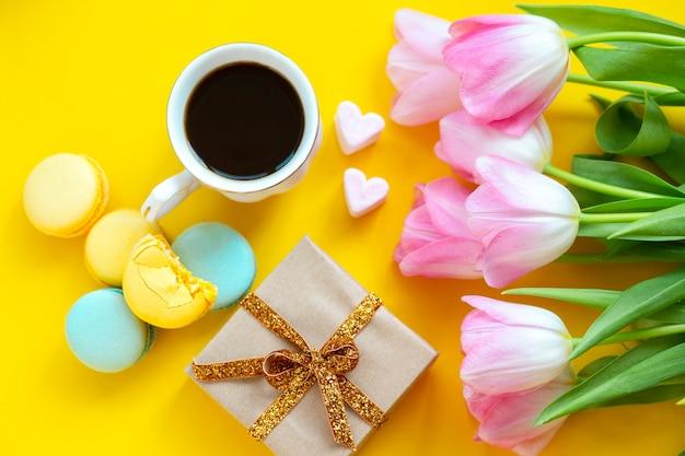 Filiżanka kawy z ciasteczkami i kwiatami. kawa z makaronikami.