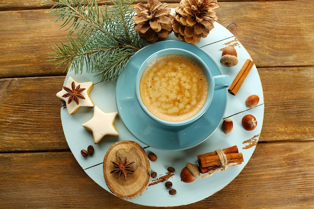 Filiżanka kawy z ciasteczkami w kształcie gwiazdy i gałęzią choinki na drewnianej macie