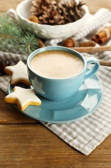 Filiżanka kawy z ciasteczkami w kształcie gwiazdy i gałęzią choinki na serwetce