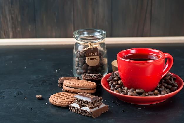 Filiżanka kawy z ciastkami i czekoladą na czarnym tle