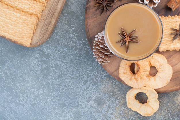 Filiżanka kawy z ciastkami i szyszkami na drewnianym talerzu. wysokiej jakości zdjęcie