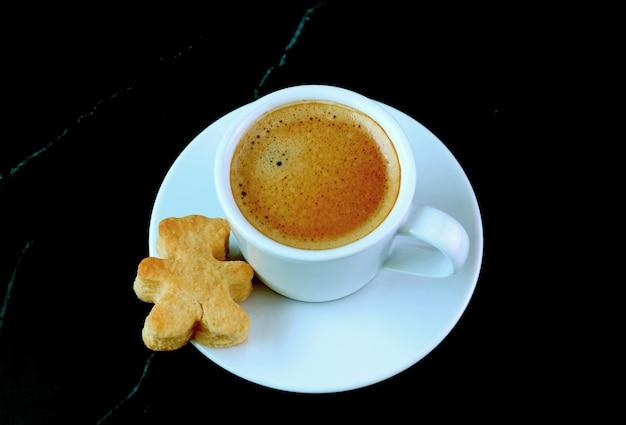 Filiżanka kawy z ciastkiem w kształcie misia na czarnym marmurowym stole