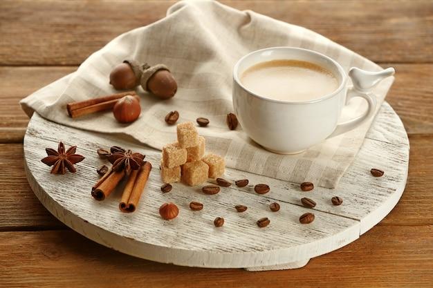 Filiżanka kawy z cukrem i cynamonem na białej drewnianej macie