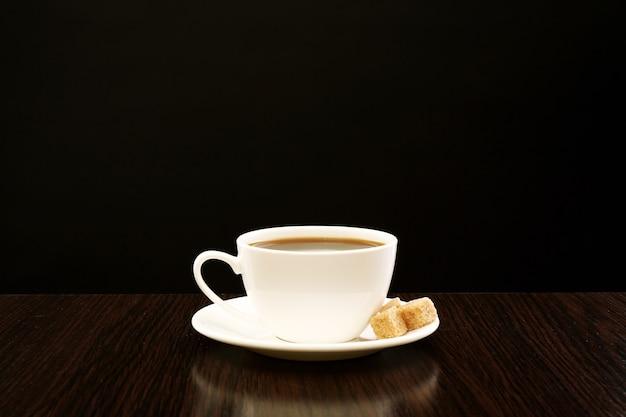 Filiżanka kawy z cukrem w kostce na drewnianym stole