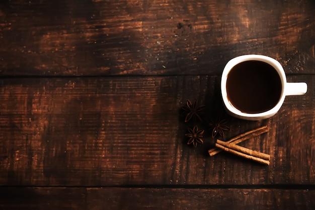 Filiżanka kawy z cynamonem na ciemnym drewnianym