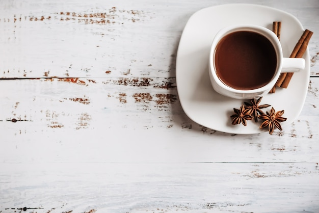 Filiżanka kawy z cynamonem na jasnym drewnianym