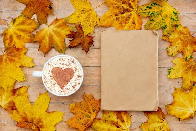 Filiżanka kawy z cynamonowym sercem i książką na stole, wokół liście klonu