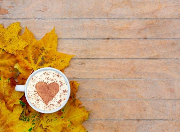 Filiżanka kawy z cynamonowym sercem na stole, wokół liście klonu