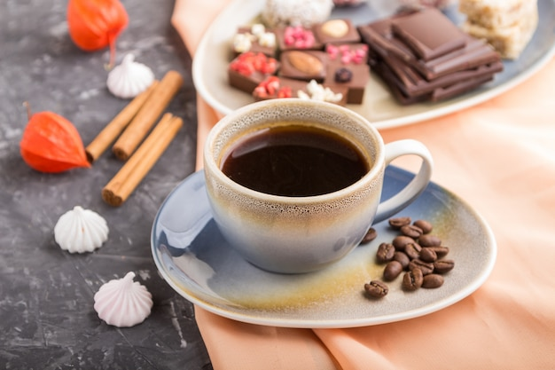 Filiżanka kawy z czekoladowymi i kokosowymi cukierkami. widok z boku