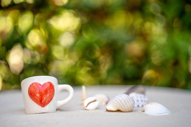 Filiżanka kawy z czerwonym sercem wydrukowanym na piasku na tle natury bokeh.