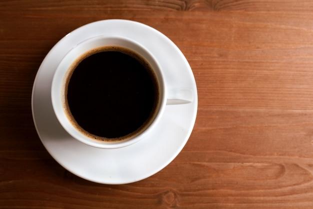 Filiżanka kawy z dymem na brązowym tle