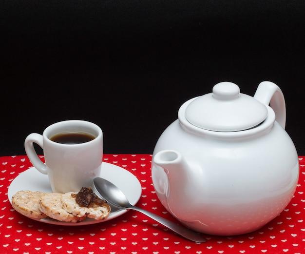 Filiżanka kawy z dzbankiem pod czerwoną tkaniną