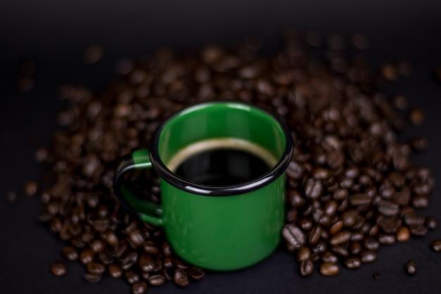 Filiżanka kawy z fasolą na ciemnym tle