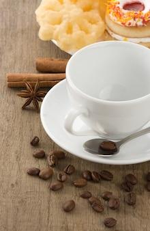 Filiżanka kawy z fasolami i ciastami na pokładzie drewna