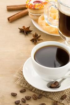 Filiżanka kawy z fasolami i ciastami na tle drewna