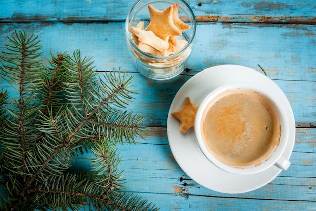 Filiżanka kawy z gałązkami choinki i ciasteczka