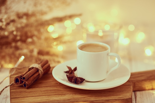 Filiżanka kawy z girlandami zaświeca i dekoracja na stole. przytulny dom koncepcja