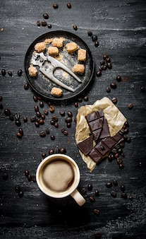 Filiżanka kawy z gorzką czekoladą i ciemnobrązowym cukrem. na czarnym tle rustykalnym.