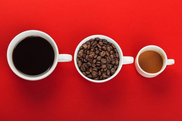 Filiżanka kawy z kawowymi fasolami na czerwonym tle.