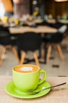 Filiżanka kawy z kreatywnie latte sztuką na drewnianym stole przy bufetem