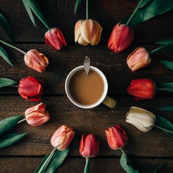Filiżanka kawy z kreatywnym układem tulipanów na ciemnej drewnianej ścianie. leżał na płasko.