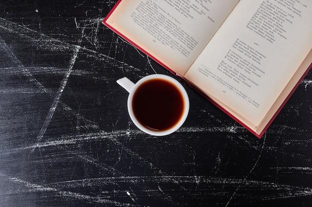 Filiżanka kawy z książką na boku.