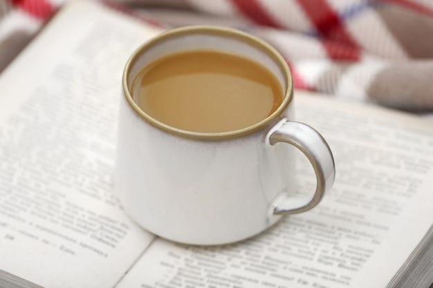 Filiżanka kawy z książką na kanapie w salonie
