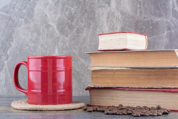 Filiżanka kawy z książkami i ziarnami kawy na marmurowym tle. zdjęcie wysokiej jakości