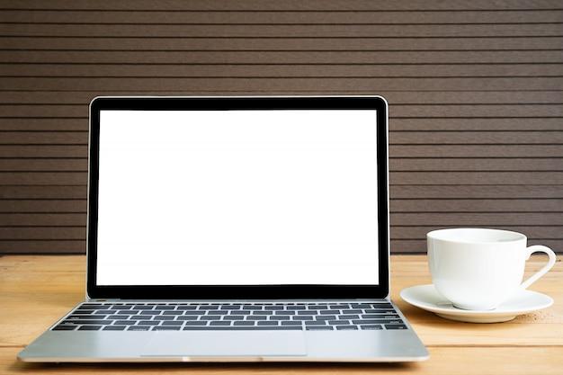 Filiżanka kawy z laptopa makieta na drewno