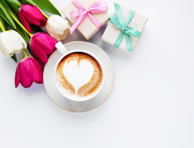 Filiżanka kawy z latte art i tulipanami