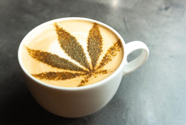 Filiżanka kawy z liściem konopi narysowana na śmietanie mlecznej.