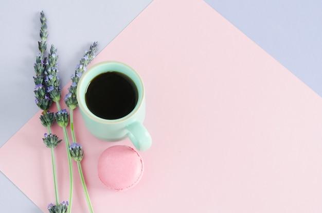 Filiżanka kawy z macarrom i lawendowymi kwiatami na fioletowym i różowym tle. widok z góry. skopiuj miejsce leżał płasko.