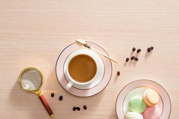 Filiżanka kawy z makaronikami i ziaren kawy na powierzchni drewnianych