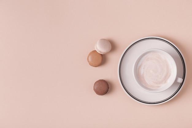 Filiżanka kawy z makaronikami na pastelowym tle
