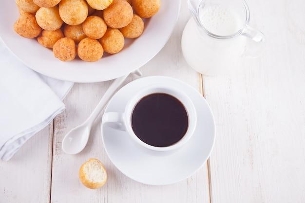 Filiżanka kawy z małymi piłkami świeżo piec domowej roboty serowy pączek w talerzu
