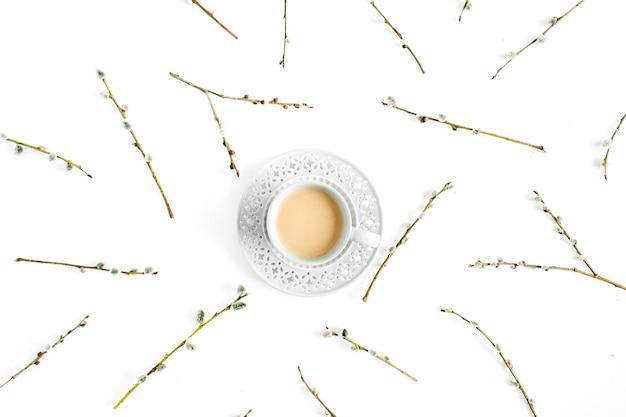 Filiżanka kawy z mleka i wierzby wzór gałązek na białym tle. płaski układanie, widok z góry