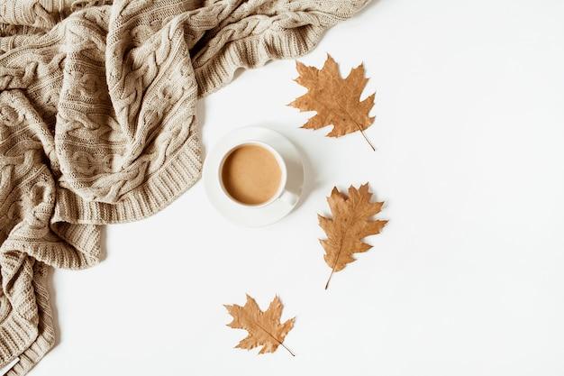 Filiżanka kawy z mlekiem, beżowa dzianina w kratę, suche liście na białym tle. widok z góry na płasko