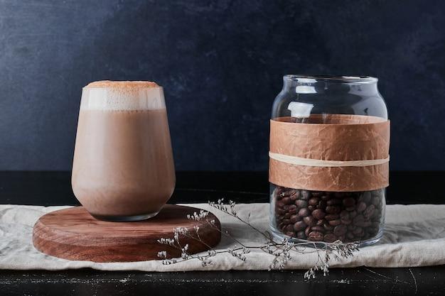 Filiżanka kawy z mlekiem i fasolą.