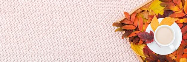 Filiżanka kawy z mlekiem i kolorowymi liśćmi na drewnianej tacy na różowym pastelowym tle z dzianiny w kratę. jesień przytulna