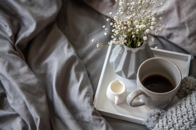Filiżanka kawy z mlekiem i kwiatami na tacy w łóżku
