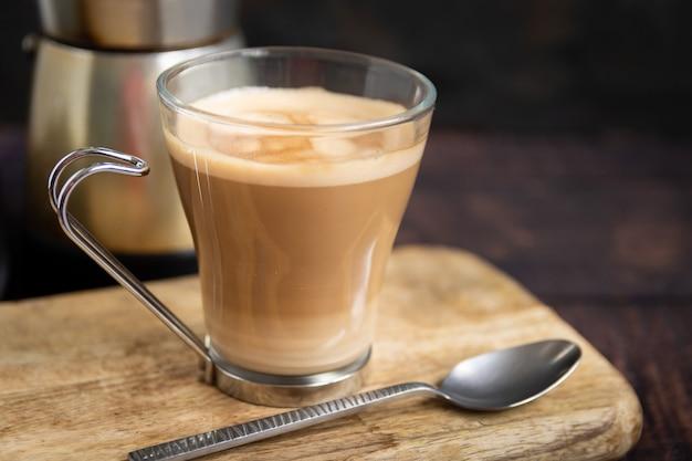 Filiżanka kawy z mlekiem i łyżeczką na drewnianym stole i włoski dzbanek do kawy w tle