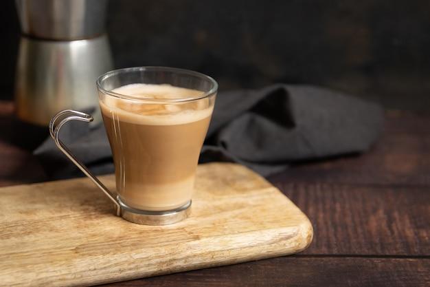 Filiżanka kawy z mlekiem na drewnianym stole i włoski dzbanek do kawy w tle