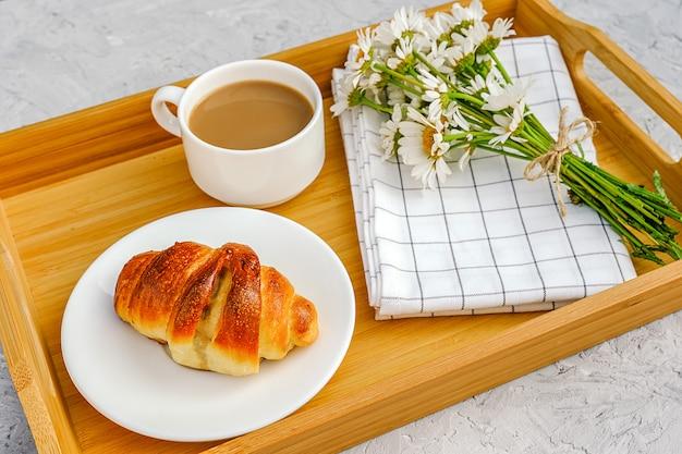 Filiżanka kawy z mlekiem, świeżo upieczony rogalik, serwetka w kratkę i kwiaty rumianku na drewnianej tacy