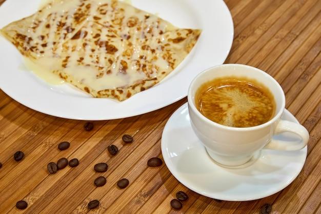 Filiżanka kawy z naleśnikiem polana skondensowanym mlekiem