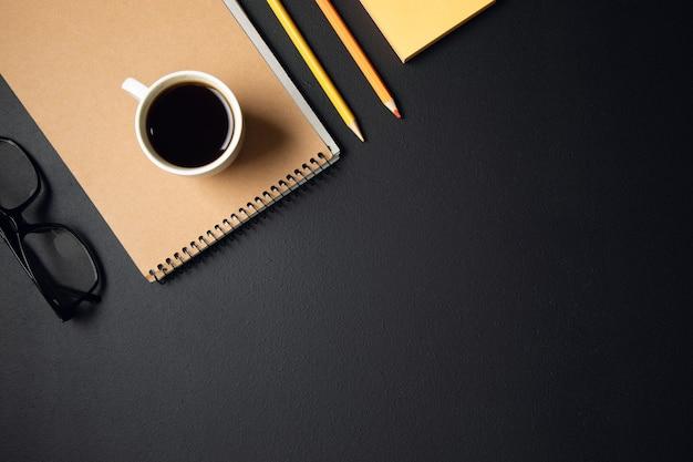 Filiżanka kawy z notatnikiem i ołówkami z papierem na stole