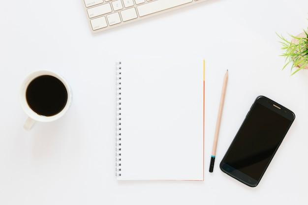 Filiżanka kawy z notebookiem i telefonem
