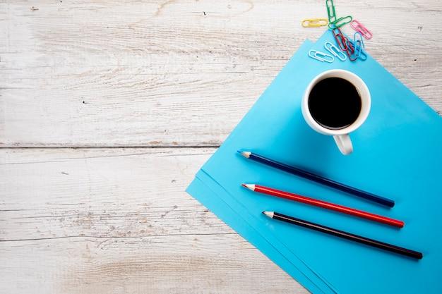 Filiżanka Kawy Z Ołówkami Na Niebieskim Papierze Na Stole Premium Zdjęcia