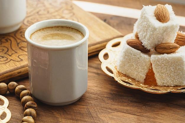 Filiżanka kawy z orientalnymi słodyczami na drewnianym stole z bliska